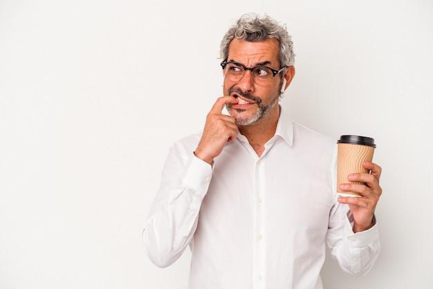 Homme d'affaires d'âge moyen tenant un café à emporter isolé sur fond blanc détendue en pensant à quelque chose en regardant un espace de copie.