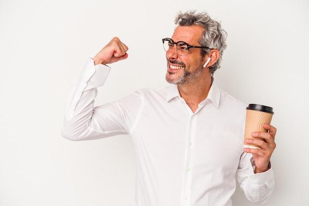Homme d'affaires d'âge moyen tenant un café à emporter isolé sur fond blanc levant le poing après une victoire, concept gagnant.