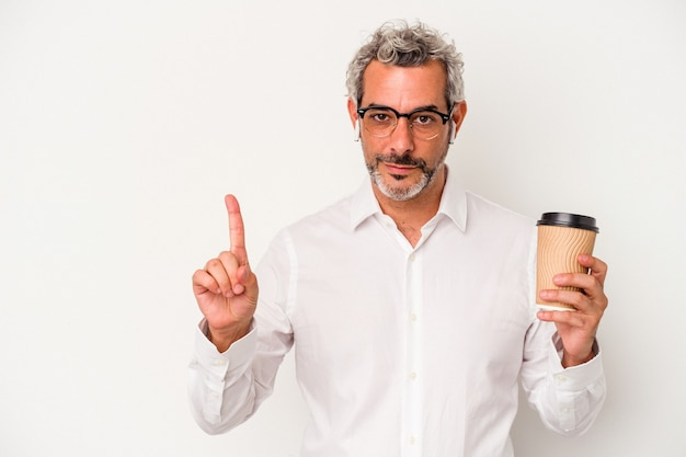 Homme d'affaires d'âge moyen tenant un café à emporter isolé sur fond blanc montrant le numéro un avec le doigt.