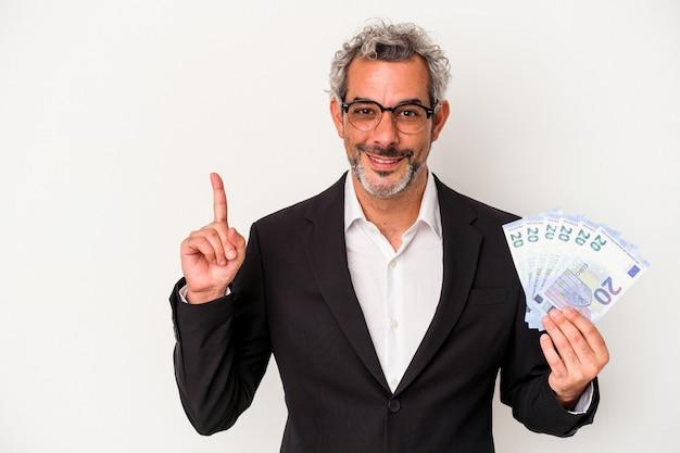 Homme d'affaires d'âge moyen tenant des factures isolées sur fond bleu montrant le numéro un avec le doigt.