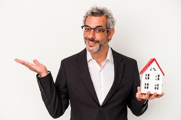 Homme d'affaires d'âge moyen tenant des factures et un modèle de maison isolé sur fond bleu montrant un espace de copie sur une paume et tenant une autre main sur la taille.