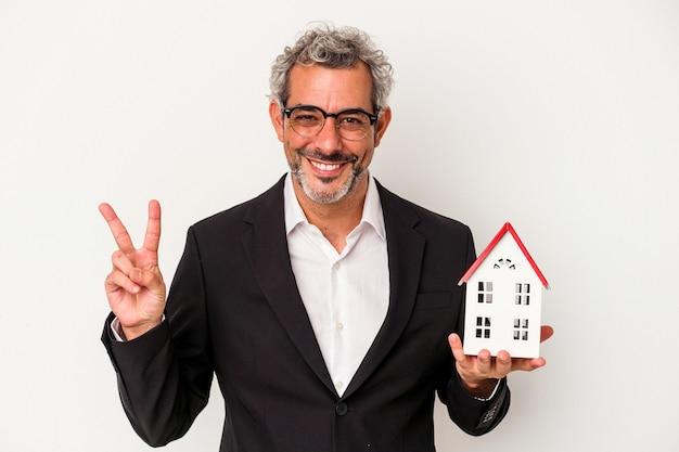 Homme d'affaires d'âge moyen tenant des factures et un modèle de maison isolé sur fond bleu montrant le numéro deux avec les doigts.