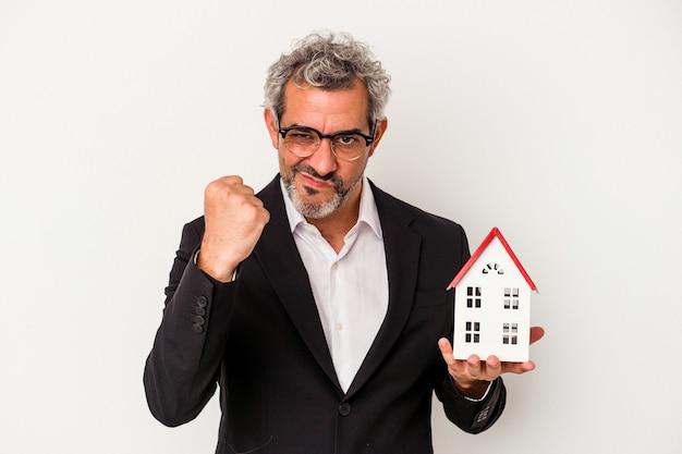 Homme d'affaires d'âge moyen tenant des factures et un modèle de maison isolé sur fond bleu montrant le poing à la caméra, expression faciale agressive.