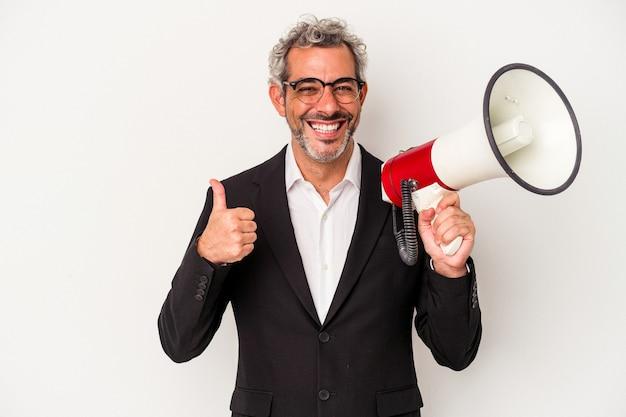 Homme d'affaires d'âge moyen tenant un mégaphone isolé sur fond blanc souriant et levant le pouce vers le haut