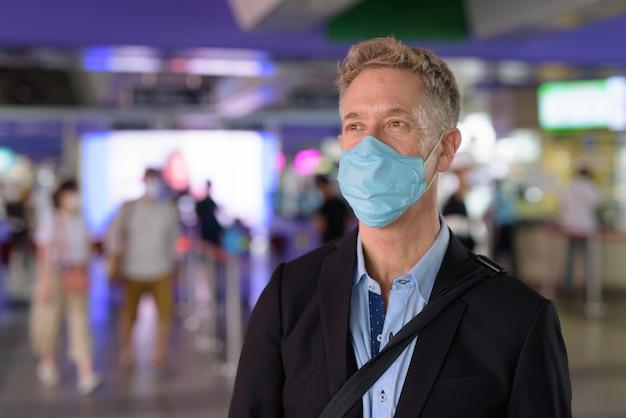 Homme d'affaires d'âge mûr avec masque à pied de la gare du ciel