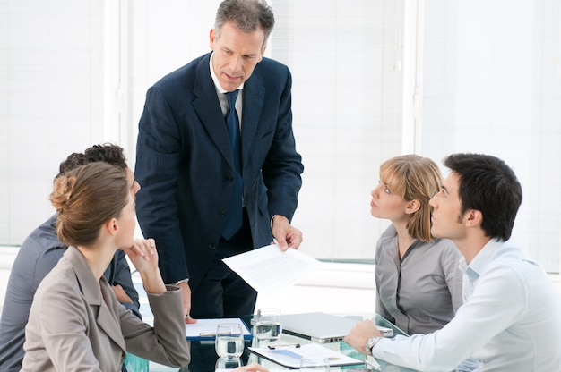 Homme d'affaires d'âge mûr parlant et expliquant sa stratégie commerciale à ses collègues au bureau