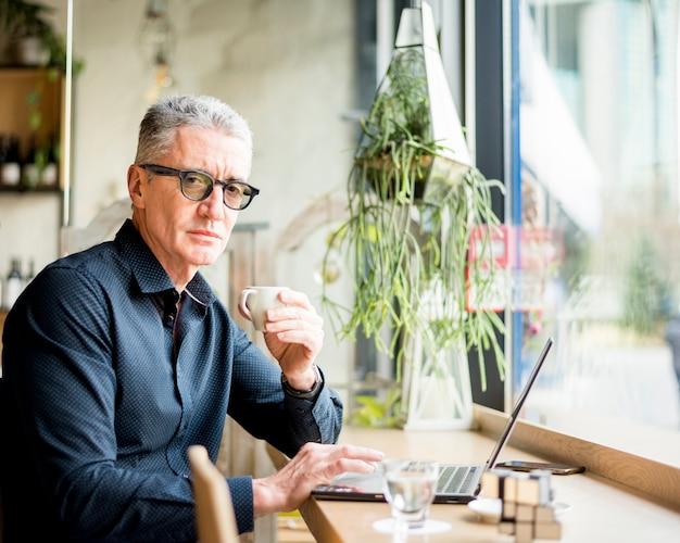 Homme d'affaires âgé posant avec un café