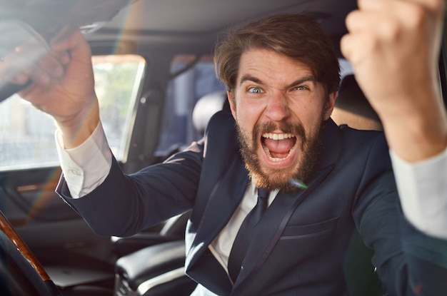 Homme d'affaires agressif regardant par la fenêtre de la voiture et faisant des gestes avec ses mains