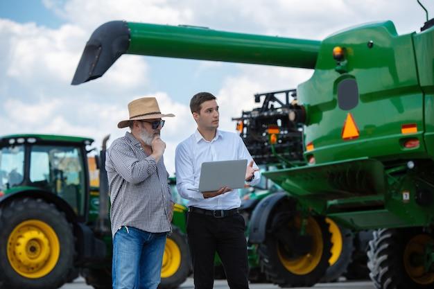 Homme d'affaires et agriculteur avec des tracteurs