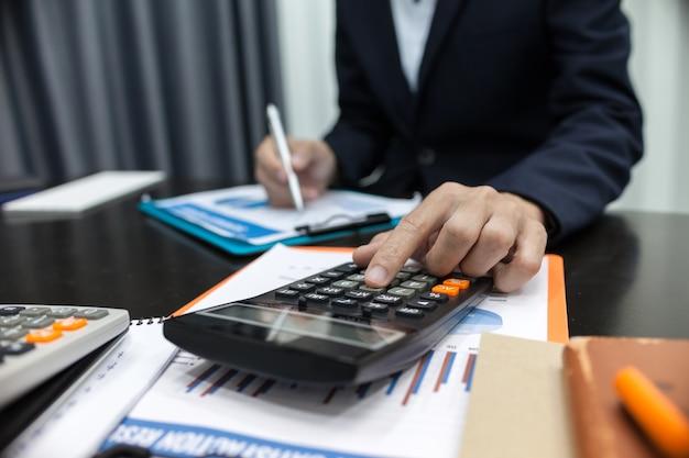 Homme d'affaires à l'aide de calcul d'affaires financières calculatrice.