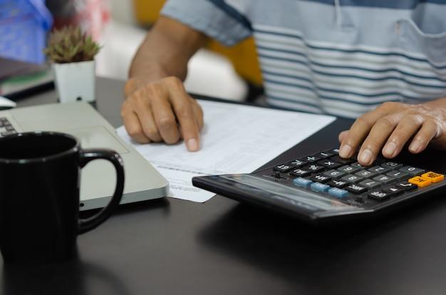 Homme d'affaires à l'aide de la calculatrice à un bureau. concepts de finance d'entreprise, de fiscalité et d'investissement.
