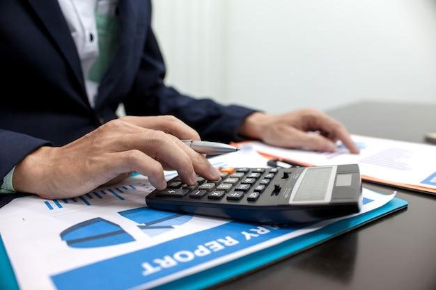 Homme d'affaires à l'aide d'une calculatrice pour calculer les comptes financiers.