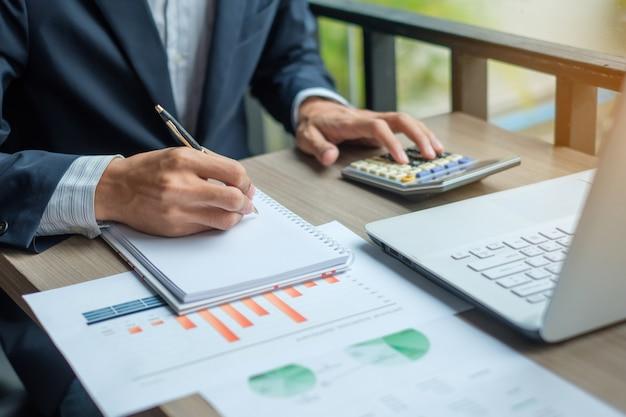 Homme d'affaires à l'aide de calcultor pour le plan de marketing d'analyse