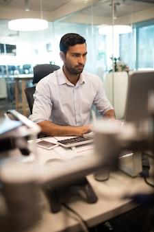 Homme d'affaires à l'aide d'ordinateur au bureau