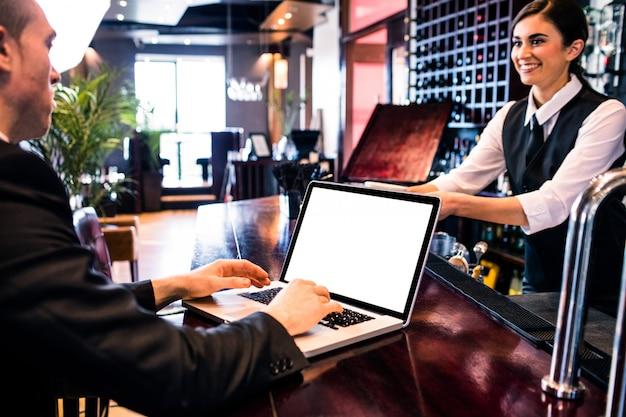 Homme d'affaires à l'aide d'un ordinateur portable au comptoir dans un bar
