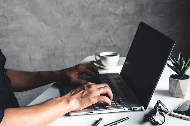 Homme d'affaires à l'aide d'un ordinateur portable et main en tapant sur le clavier de l'ordinateur portable avec des lunettes de stylo et une tasse de café chaud