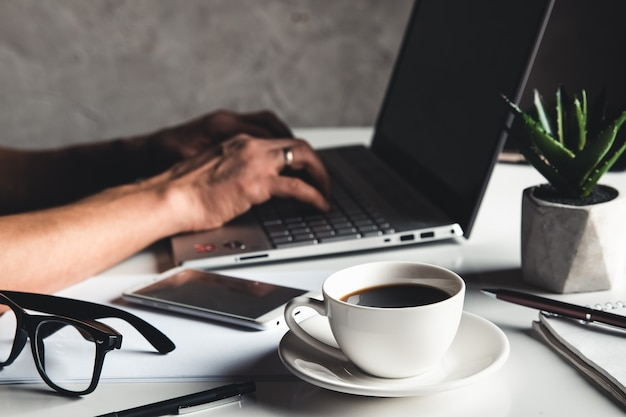 Homme d'affaires à l'aide d'un ordinateur portable et de la saisie à la main sur le clavier d'un ordinateur portable avec des lunettes de stylo et une tasse de café chaud