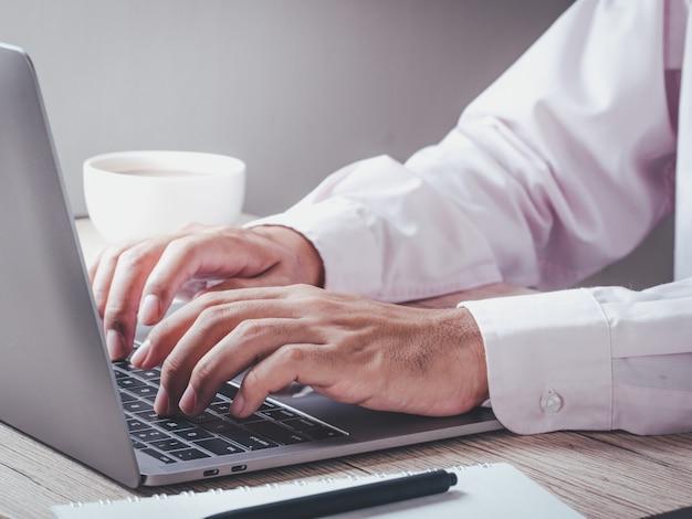 Homme d'affaires à l'aide d'un ordinateur portable travaillant sur une nouvelle idée de projet à son bureau au bureau le matin