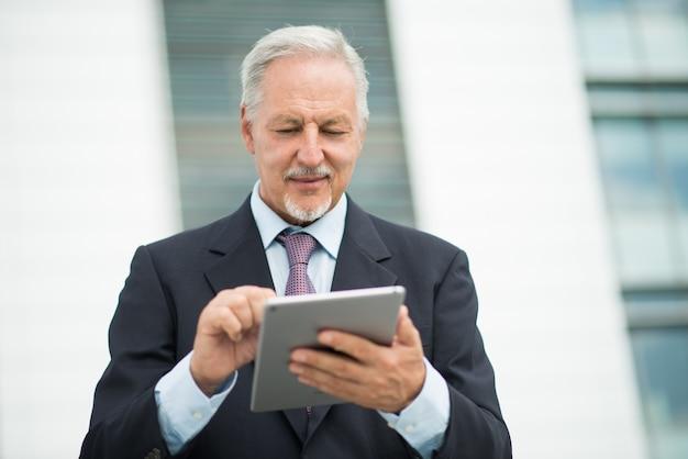 Homme d'affaires à l'aide de sa tablette en plein air