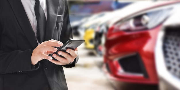 Homme d'affaires à l'aide de smartphone sur fond flou de la nouvelle voiture affichée dans le showroom dealer avec espace copie.