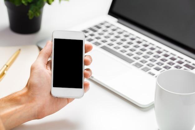 Homme d'affaires à l'aide de son smartphone avec écran blanc dans un bureau en gros plan