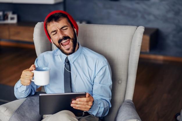 Homme d'affaires à l'aide de tablette, boire du café à la maison.