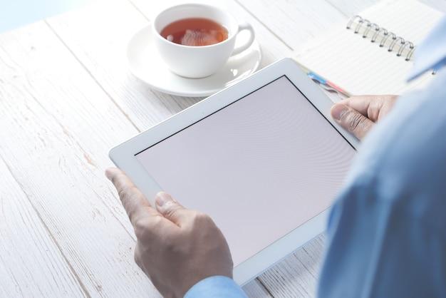 Homme d & # 39; affaires à l & # 39; aide de la tablette numérique sur le bureau