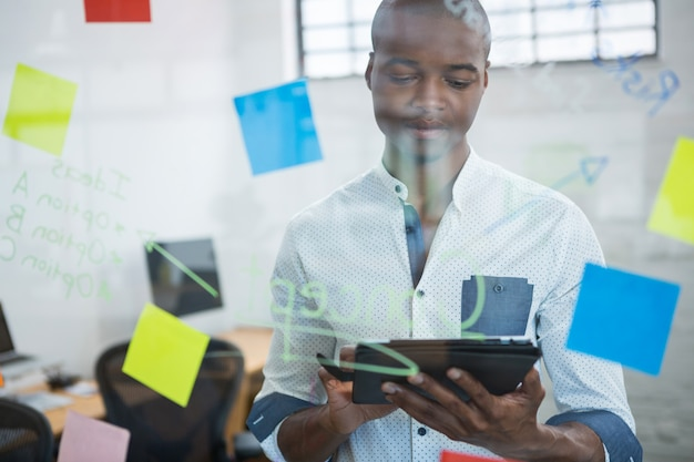 Homme d'affaires à l'aide de tablette numérique lors de l'écriture sur pense-bête