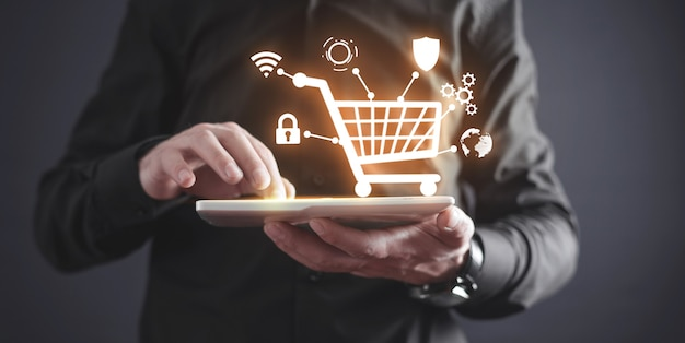 Homme d'affaires à l'aide de tablette avec panier. commerce électronique. shopping en ligne