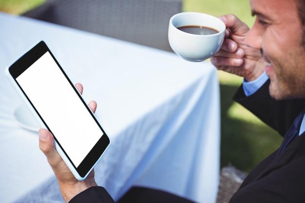 Homme d'affaires à l'aide d'une tablette et prendre un café