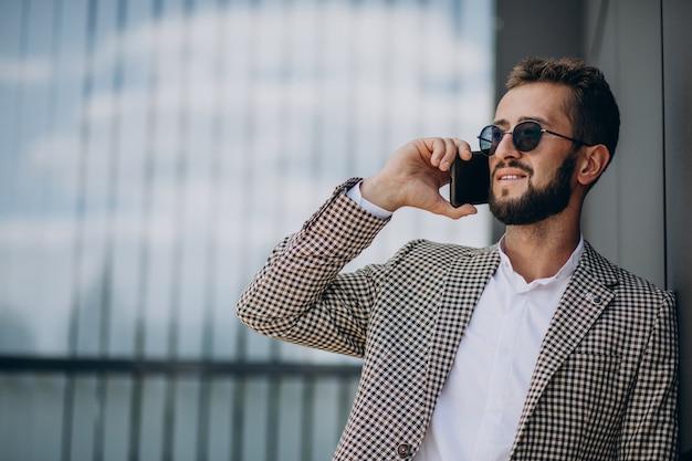Homme d'affaires à l'aide de téléphone à l'extérieur du centre de bureau