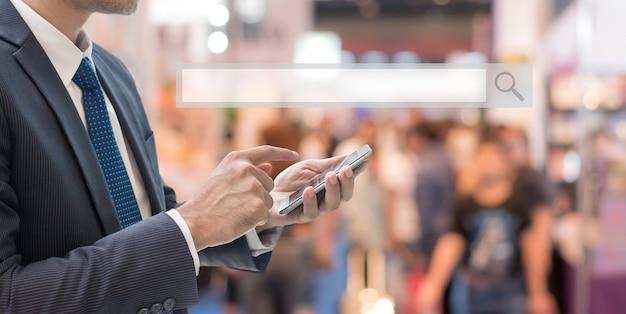 Homme d'affaires à l'aide de téléphone intelligent avec barre de recherche vide dans le hall d'exposition des foires commerciales