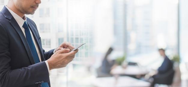 Homme d'affaires à l'aide de téléphone intelligent dans l'arrière-plan de la bannière espace bureau et espace copie.