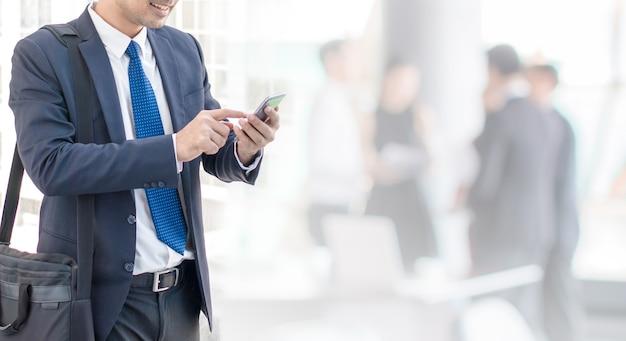 Homme d'affaires à l'aide de téléphone intelligent dans le fond de l'espace de bureau et de l'espace de copie.