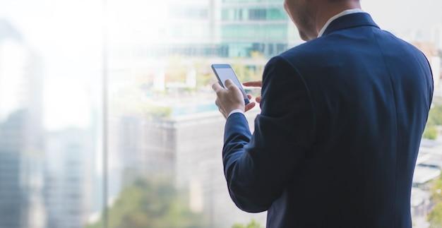 Homme d'affaires à l'aide de téléphone intelligent sur la fenêtre avec fond de bâtiment de la ville et de l'espace de copie.