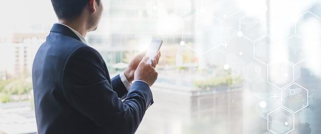 Homme d'affaires à l'aide de téléphone intelligent sur la fenêtre avec forme de connexion de technologie futuriste sur le fond de connexion réseau
