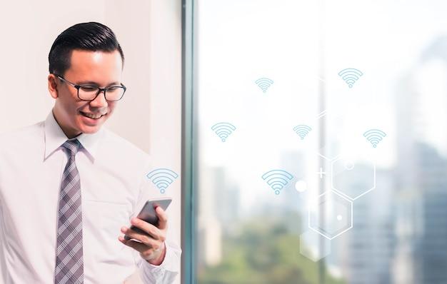 Homme d'affaires à l'aide de téléphone intelligent avec l'icône wifi sur fond d'espace de bureau intérieur flou.