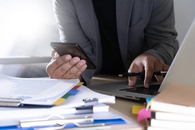 Homme d'affaires à l'aide de téléphone intelligent téléphone et ordinateur portable