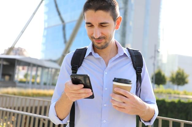 Homme d'affaires à l'aide de téléphone portable et boire du café dans la ville