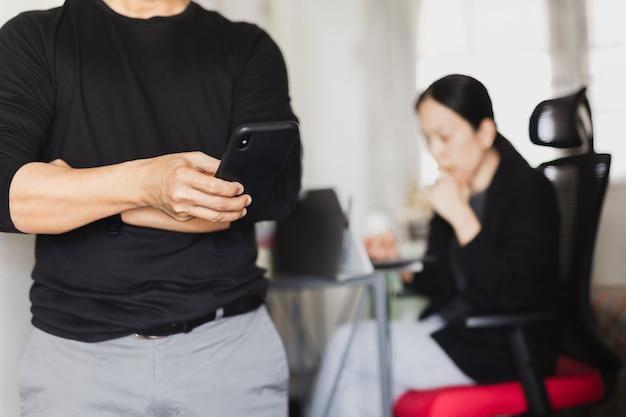 Homme d'affaires à l'aide de téléphone portable pendant que la femme travaille en arrière-plan.