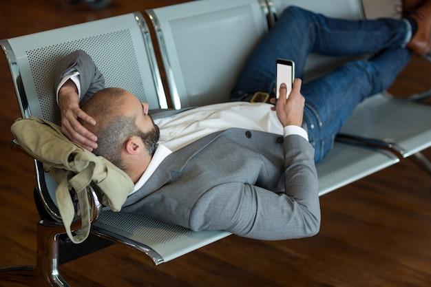 Homme d'affaires à l'aide de téléphone portable en position couchée sur des chaises dans la zone d'attente