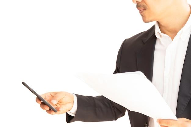 Homme d'affaires à l'aide de téléphone portable travaillant avec un tracé de détourage isolé de documents.