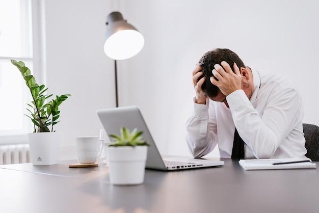 Homme d'affaires aîné frustré, assis sur le bureau avec la main sur la tête au bureau.
