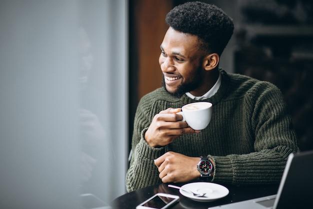 Homme d'affaires américain avec ordinateur portable dans un café