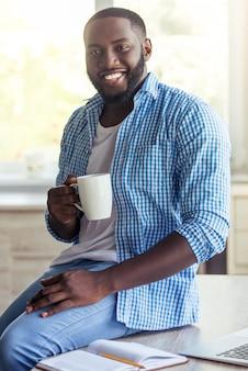 Homme d'affaires américain en vêtements décontractés tient une tasse.