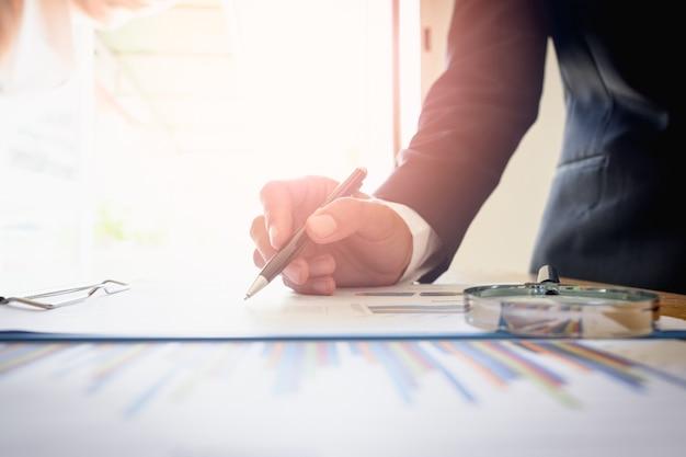 Homme d'affaires analysant le graphique avec la feuille de graphique sur le bureau