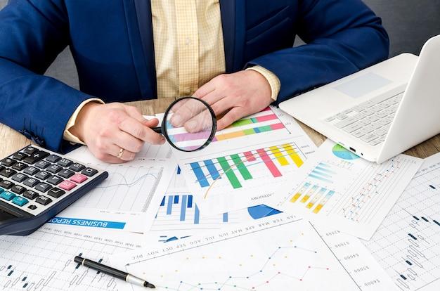 Homme d'affaires analysant des graphiques commerciaux avec une loupe