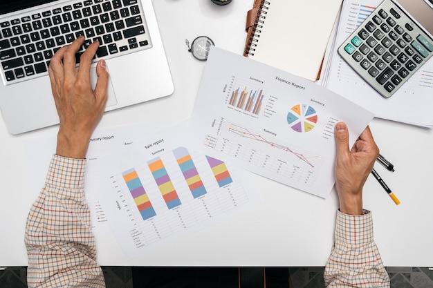 Homme d'affaires, analyse des graphiques d'investissement avec ordinateur portable sur la table de bureau.