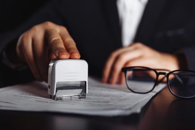 Homme d'affaires approuve un contrat important. documents et timbres sur le bureau. concept d'entreprise.