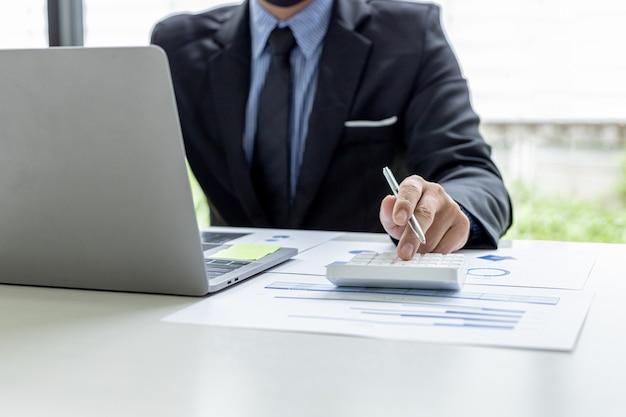 L'homme d'affaires appuie sur une calculatrice blanche, il est le propriétaire de l'entreprise, il vérifie les documents financiers de l'entreprise dans son bureau, les documents financiers affichent le format graphique. concept de gestion financière